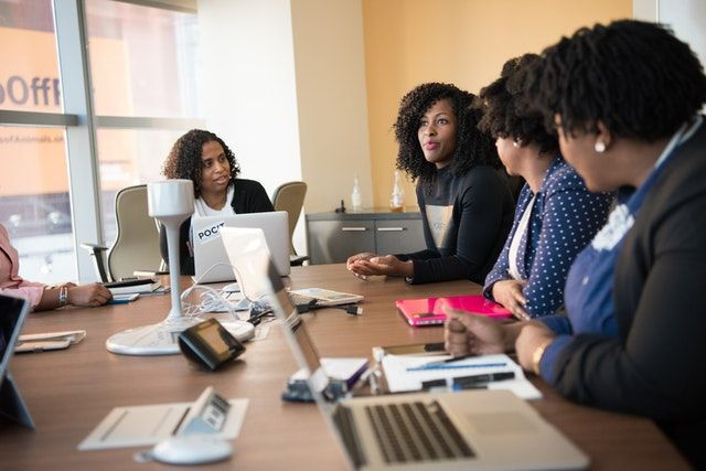 Group of peple having a meeting at a conference table filled with laptops and notepads