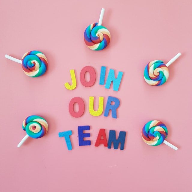 The words 'JOIN OUR TEAM' spelled out with magnetic letters. Multi colored lollipops surround the words.